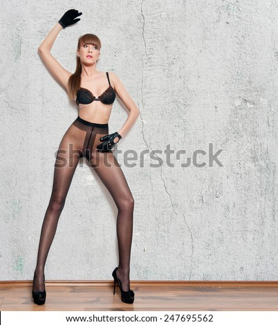 Attractive red hair model with pantyhose and black gloves standing on gray wall. Fashion portrait of sensual long legs woman - indoor shoot. Sensual female in pantyhose posing provocatively. - stock photo