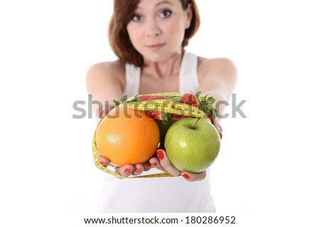 attractive red hair woman holding a mix of fruit  in hands bond with measure tape in slave to diet concept isolated on white background - stock photo