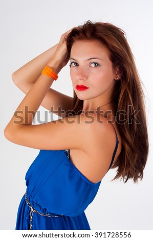 Attractive red-haired girl with freckles wearing blue dress over white background - stock photo