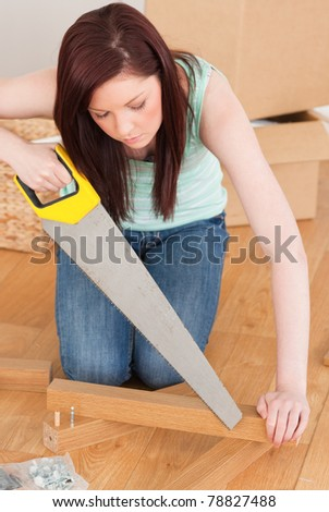 Attractive red-haired woman using a saw for diy at home - stock photo