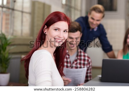 Attractive redhead businesswoman working in a busy friendly office with smiling colleagues in the background - stock photo