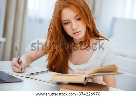Attractive redhead woman doing homework at home - stock photo