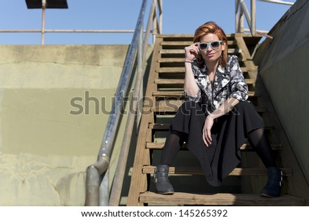 Attractive redhead woman sitting on wooden steps