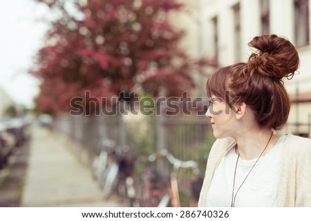 Attractive redhead woman with a fun hairstyle with her long hair wound into a high bun or top knot standing in an urban street, profile view with copyspace - stock photo