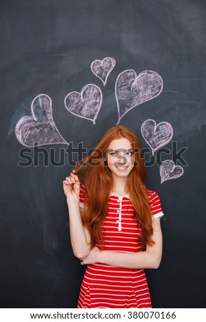 Attractive redhead young woman standing over blackboard with drawn hearts behind her - stock photo