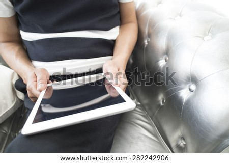 Attractive relaxed and man is surfing on his tablet - stock photo
