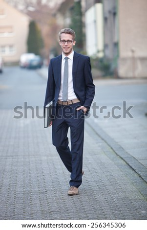 Attractive relaxed businessman wearing glasses walking across a paved street with his hand in his pocket and file under his arm looking at the camera with a smile