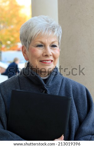 Attractive Retired Senior Citizen Business Woman Who is Mature and Pretty and Smiling and Holding a Folder and Smiling - stock photo
