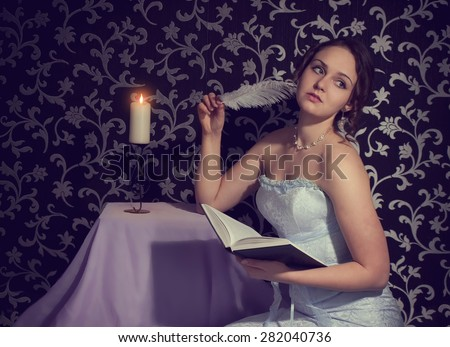 Attractive romantic girl reading book and writing a poem and verses by feather (pen) by candle light as symbol of beauty, creation, art, education, studying, skill, seduction, sex, youth, adolescence - stock photo