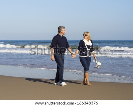 Attractive romantic mature couple walking along the beach hand in hand at the edge of the sea enjoying the beauty of the seaside and tranquillity of nature - stock photo