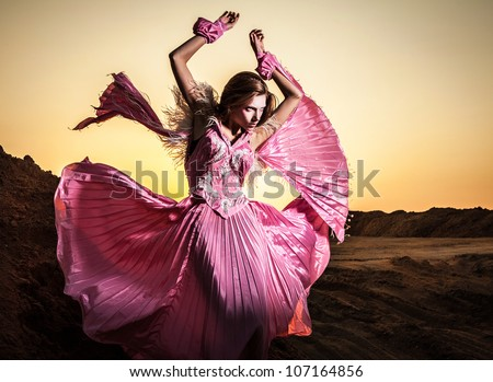 Attractive romantic woman on beautiful pink dress pose outdoor. - stock photo