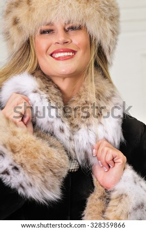 Attractive Russian woman wearing a fashionable fur coat and fur hat - stock photo