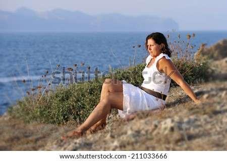 attractive 40s mature woman sitting alone on the beach thinking and looking at sea horizon pensive and thoughtful on a relaxing and peaceful summer evening enjoying vacation - stock photo
