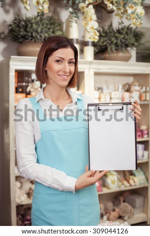 Attractive saleswoman is standing in her flower shop. She is holding a folder with order of customer and showing this paper to the camera proudly. The woman is smiling