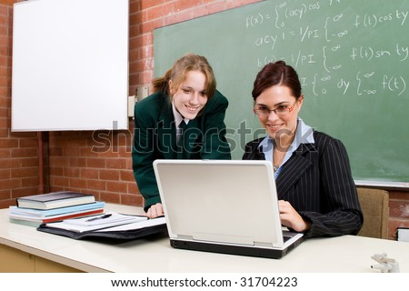 attractive school teacher teaching computer lesson to her students - stock photo