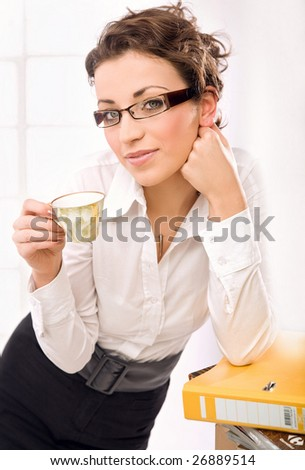 Attractive secretary drinking coffee - stock photo