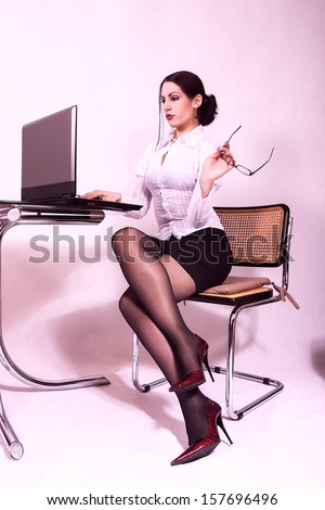 attractive secretary working on a lap top computer - stock photo