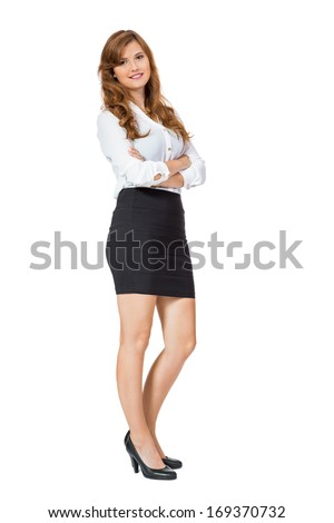 Attractive self-assured trendy young businesswoman wearing high heels and a black miniskirt standing with folded arms smiling at the camera, side view isolated on white - stock photo