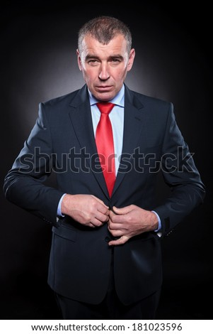 attractive senior business man buttoning his coat and looks at the camera - stock photo
