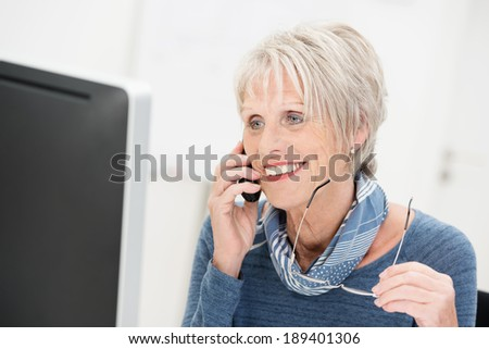 Attractive senior businesswoman chatting on the phone smiling as she listens to the call while holding her glasses in her hand - stock photo