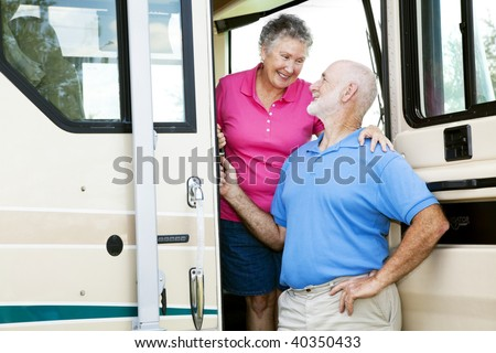 Attractive senior couple traveling by motor home. - stock photo