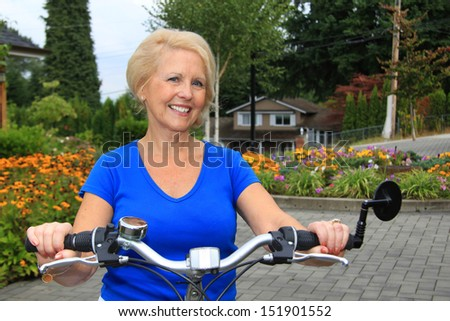 Attractive senior lady on a bicycle.  - stock photo