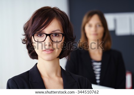 Attractive senior partner or manageress wearing glasses posing in front of her colleague in an office, close up head and shoulders portrait - stock photo
