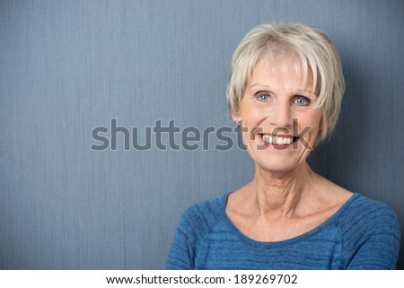 Attractive senior woman with a happy smile and twinkling blue eyes posing on a blue background with copyspace, head and shoulders portrait - stock photo