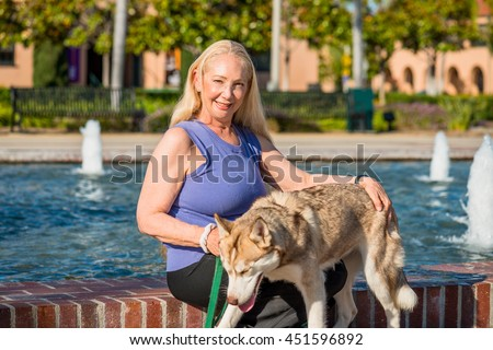 Attractive senior woman with her husky dog; outdoors, dog lover - stock photo