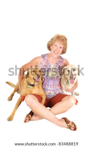 Attractive senior woman with her labrador retriever dogs on a white background - stock photo