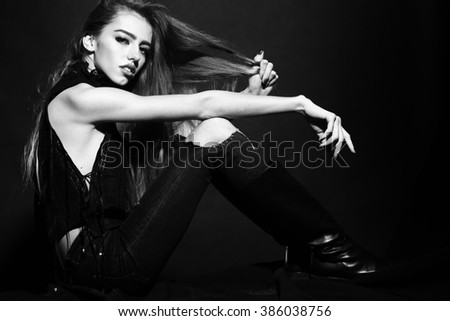 Attractive sensual young fashionable woman in stylish cloth and torn jeans with long lush hair sitting indoor on studio background black and white, horizontal picture