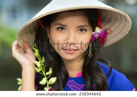 Attractive serious young Vietnamese woman in a conical straw hat with a fresh flower in her hair looking at the camera with her hand to the brim - stock photo