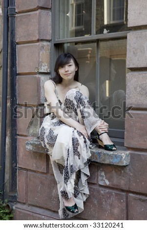 attractive serious young woman sitting at old window in London