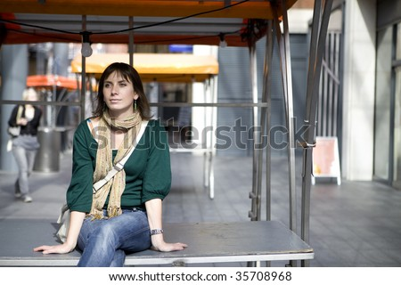 attractive serious young woman sitting on counter in market