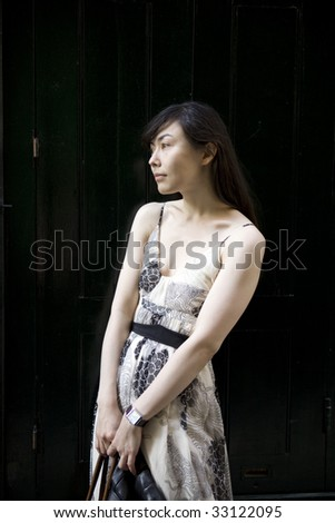 attractive serious young woman standing at old door on stairs in London. Woman`s problem