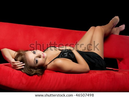 Attractive sexual girl on a red couch.