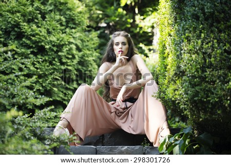 Attractive sexual young woman with bright makeup and long curly brunette hair in summer overalls with deep decollete sitting in green garden holding finger near lips sunny day, horizontal picture - stock photo