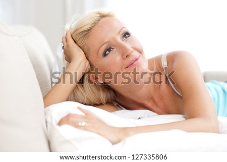 attractive sexy adult woman at her bed thinking
