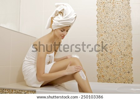 Attractive sexy and sensuality young adult beautiful brunette woman with white towel applying moisturizer cream on the long legs in home bathroom - stock photo