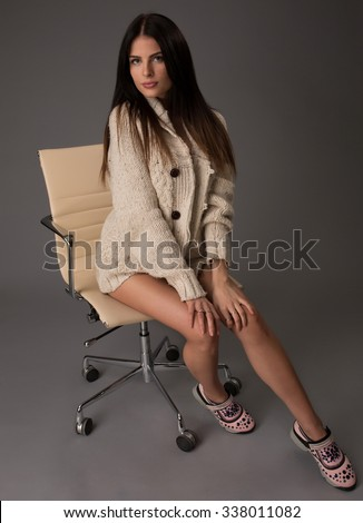 Attractive sexy brunette female with bright sweater and black stockings posing smiling sitting on office chair. Portrait of sensual fair hair woman with long legs isolated on grey background - stock photo