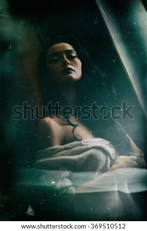 Attractive sexy brunette half naked posing provocatively in window frame. Portrait of sensual woman in classic boudoir scene. Woman with long hair daydreaming and enjoying the bright day light - stock photo