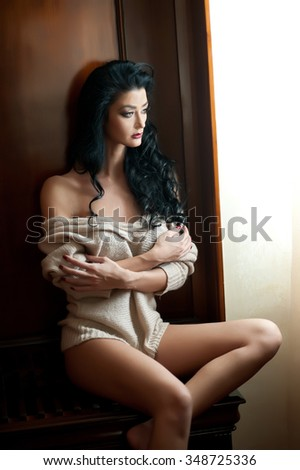 Attractive sexy brunette posing provocatively in window frame. Portrait of sensual woman in classic boudoir scene. Woman with long hair daydreaming and enjoying the bright day light - stock photo