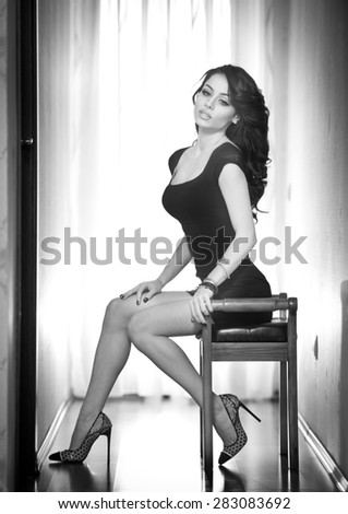 Attractive sexy brunette with long legs sitting on a chair with daylight in background. Portrait of sensual woman wearing a short black dress an high heels shoes, black and white photo - stock photo