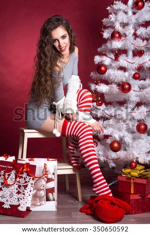 Attractive sexy girl in Christmas. next to the Christmas tree and gifts