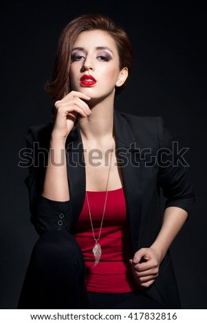 Attractive sexy girl with red lips in black jacket on dark background. Woman with short hair, the chain around his neck.