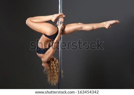 Attractive sexy woman pole dancer performing against grey background - stock photo