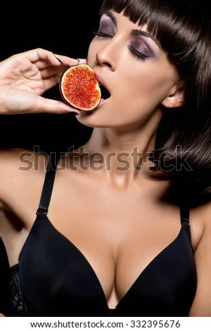 Attractive sexy woman with a fig  - stock photo