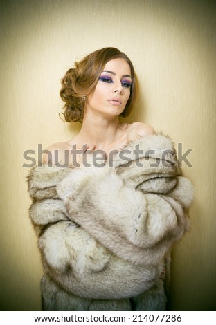 Attractive sexy young woman wearing a fur coat posing provocatively indoor. Portrait of sensual female with creative haircut, studio shot. Beautiful girl covered only with a fur exposing her shoulders - stock photo