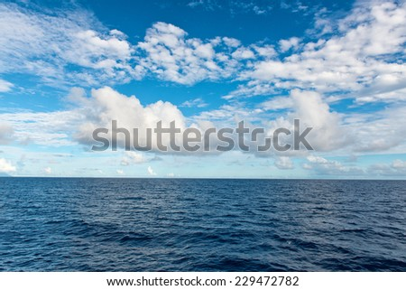 Attractive Seychelles Island Sea Horizon with Blue Sea Water and Light Blue and White Sky Above. - stock photo