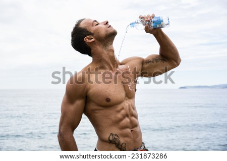 Attractive shirtless muscleman on the beach pouring down water on his chest from plastic bottle - stock photo